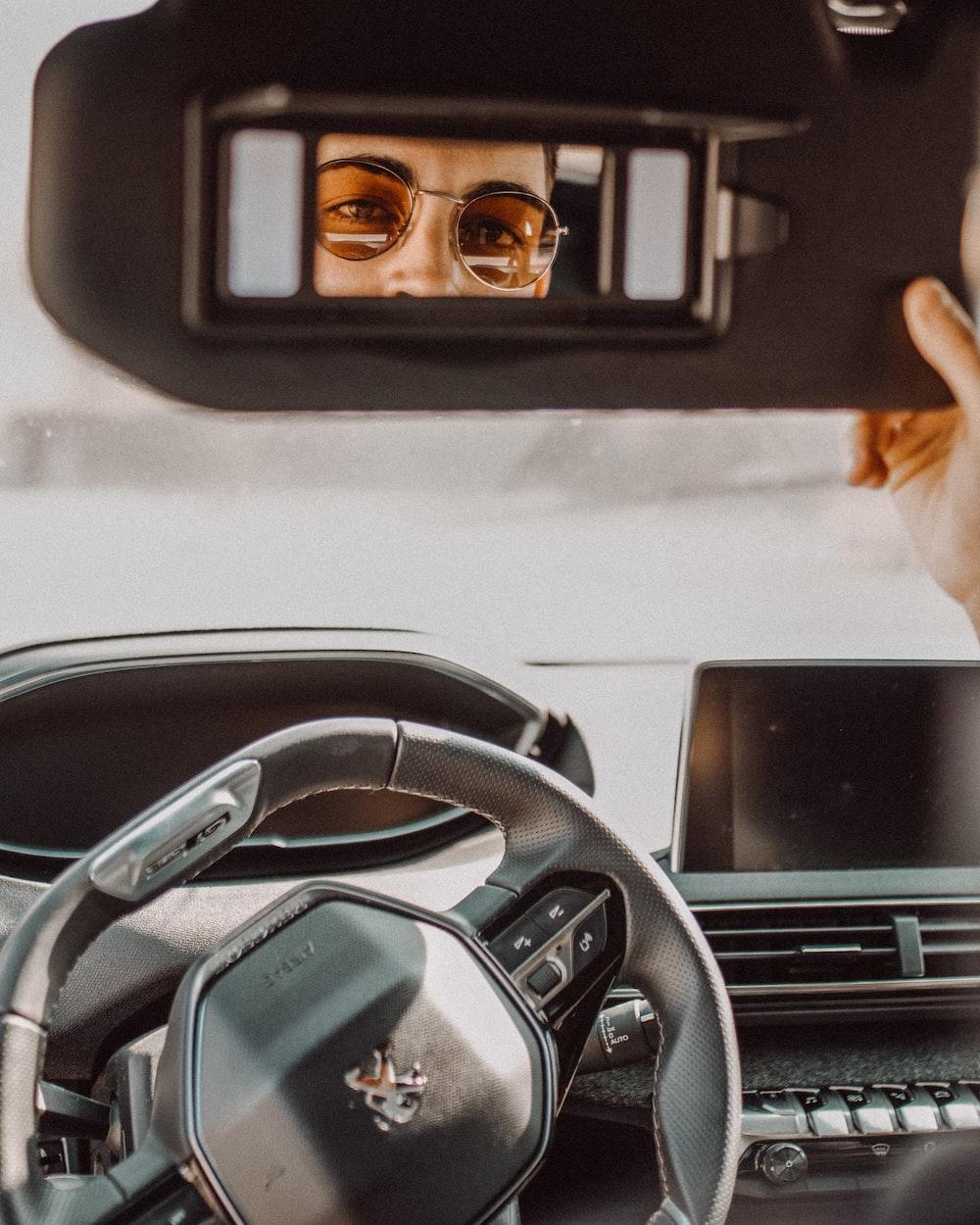man looking through Peugeot vehicle sun shade's mirror