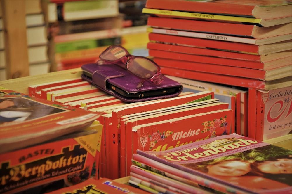 eyeglasses on smartphone in flip case on books