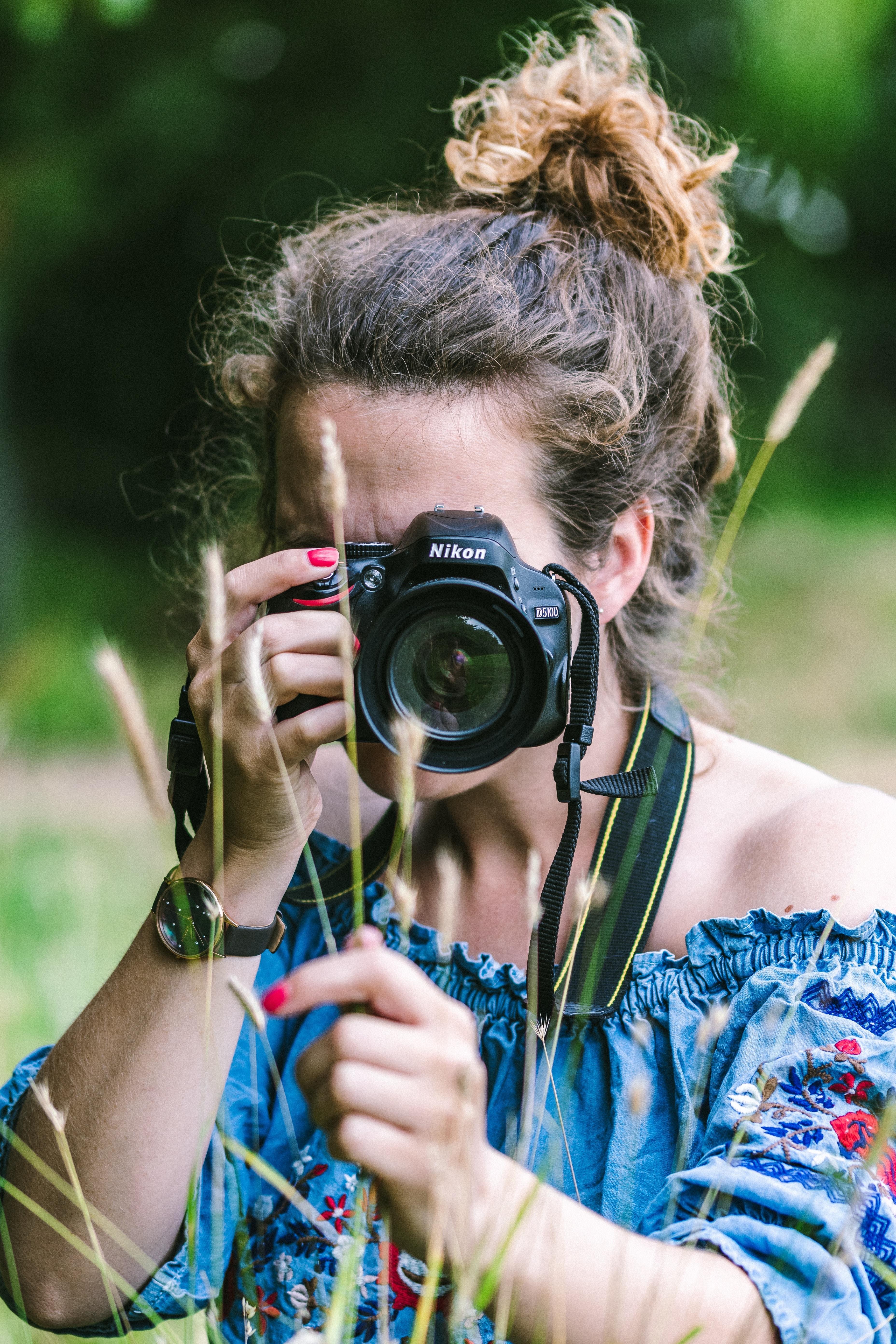 woman wearing blue dress holding camera during daytime