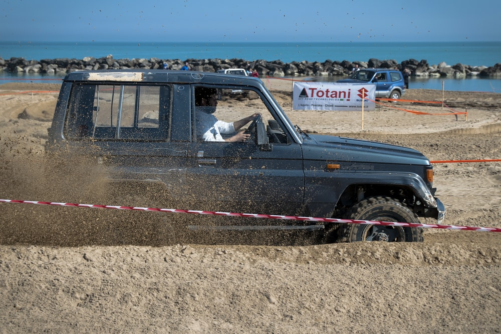 man driving mini USB on mud obstacle overlooking sea at daytime