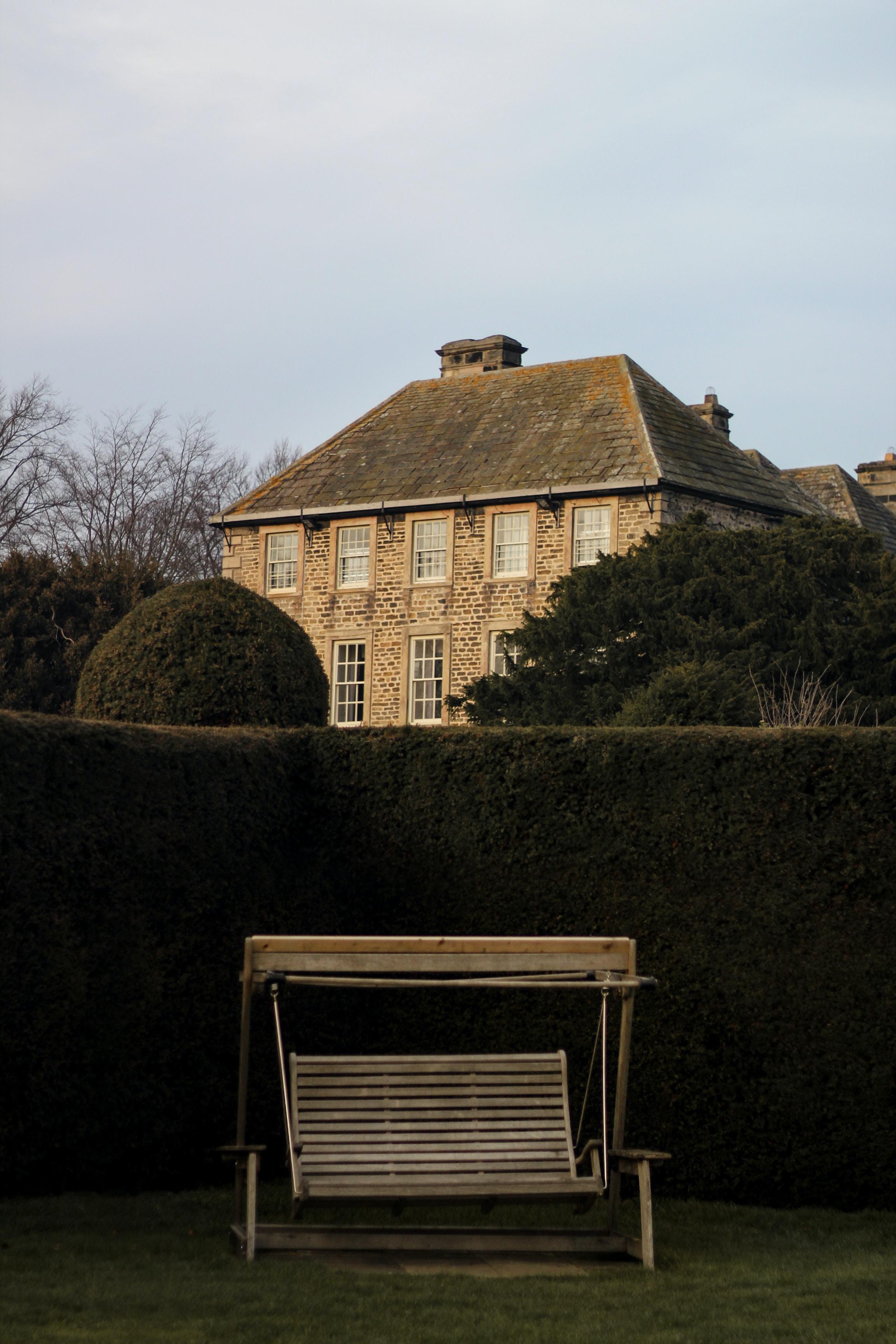 brown house near green hedge