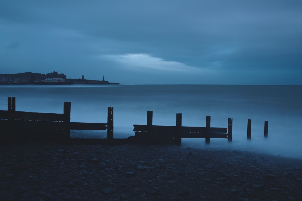 broken dock on shore under cloudy sky at dawn