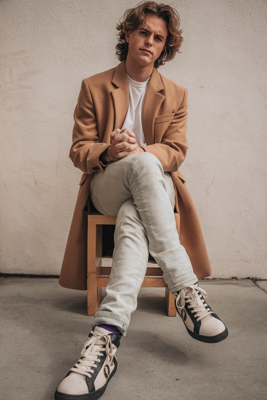 man sitting on chair wearing brown coat