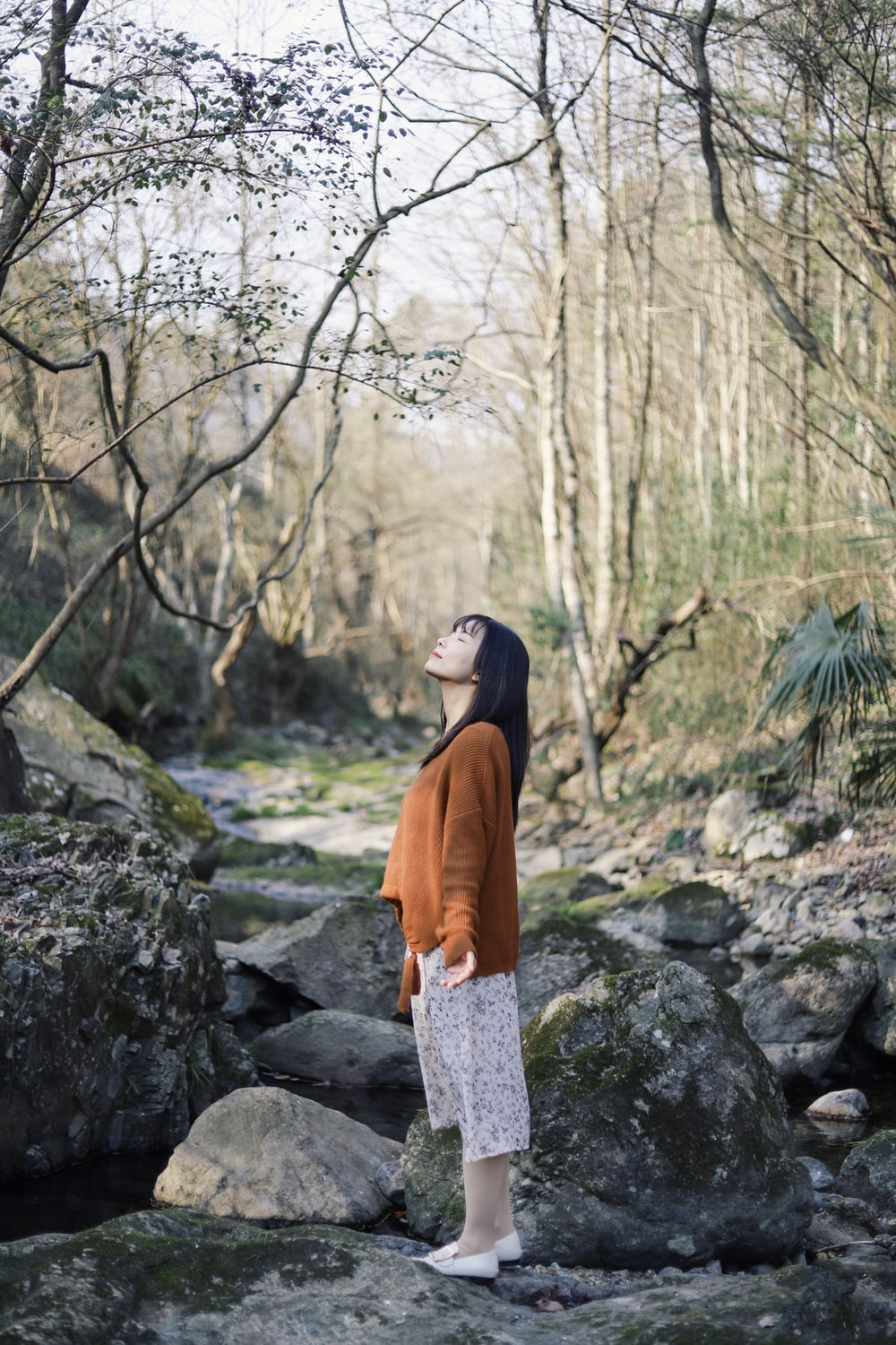 woman standing at the rock in the middle of the forest
