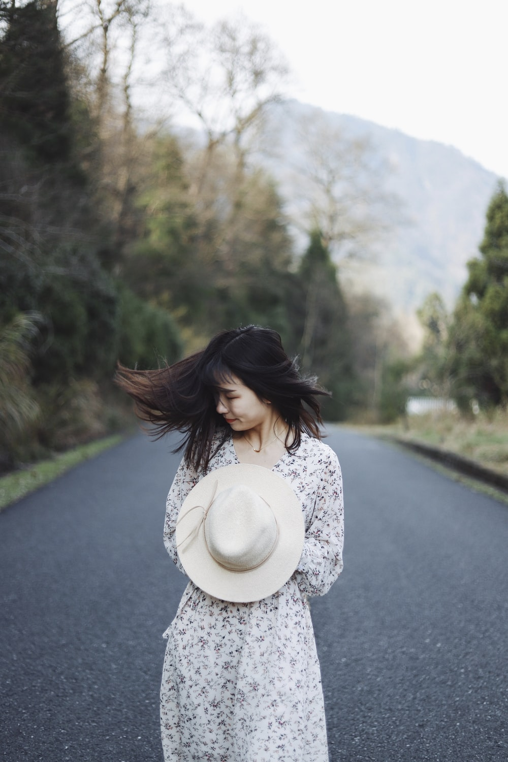 woman holding her white hat outdoort