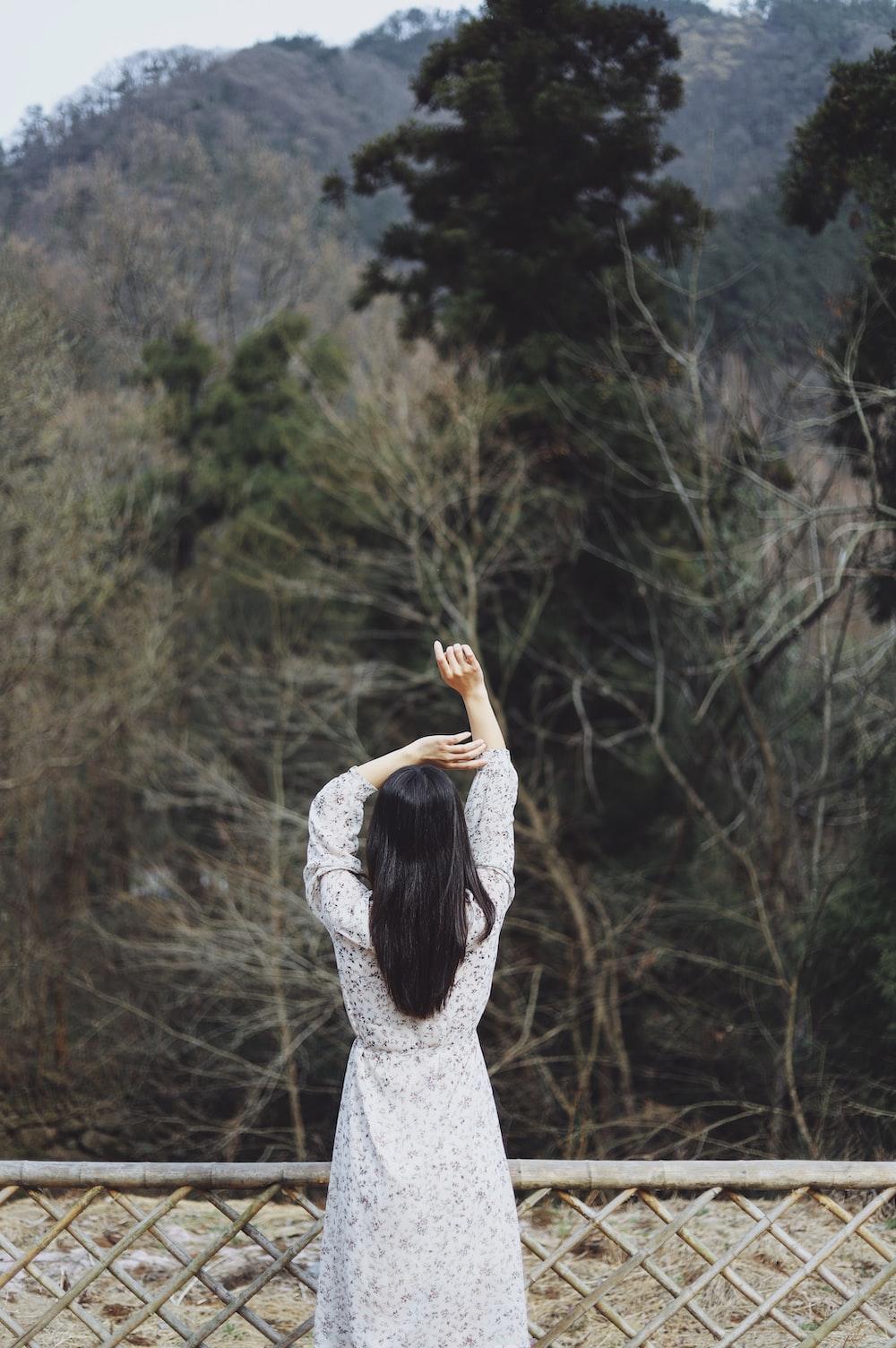 woman raised both hands near fence