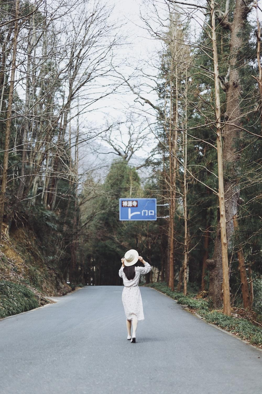 woman walking on road between bare trees