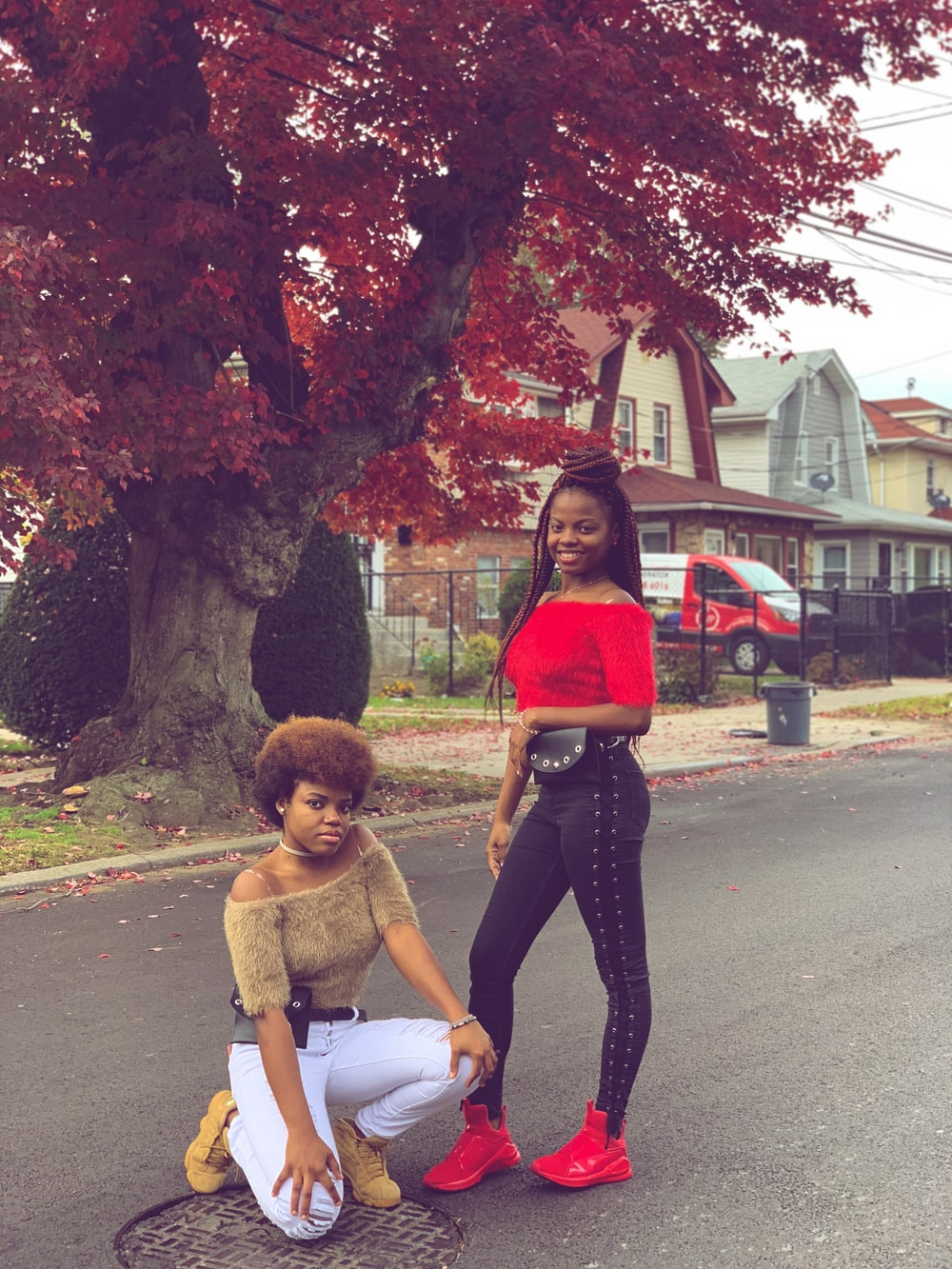 two women posing on road under tree during daytime