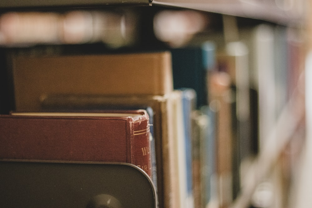 selective focus photography of books in bookshelf