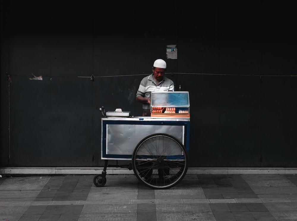man vending food near wall during daytime