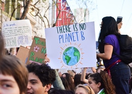 person holding there is no planet b poster