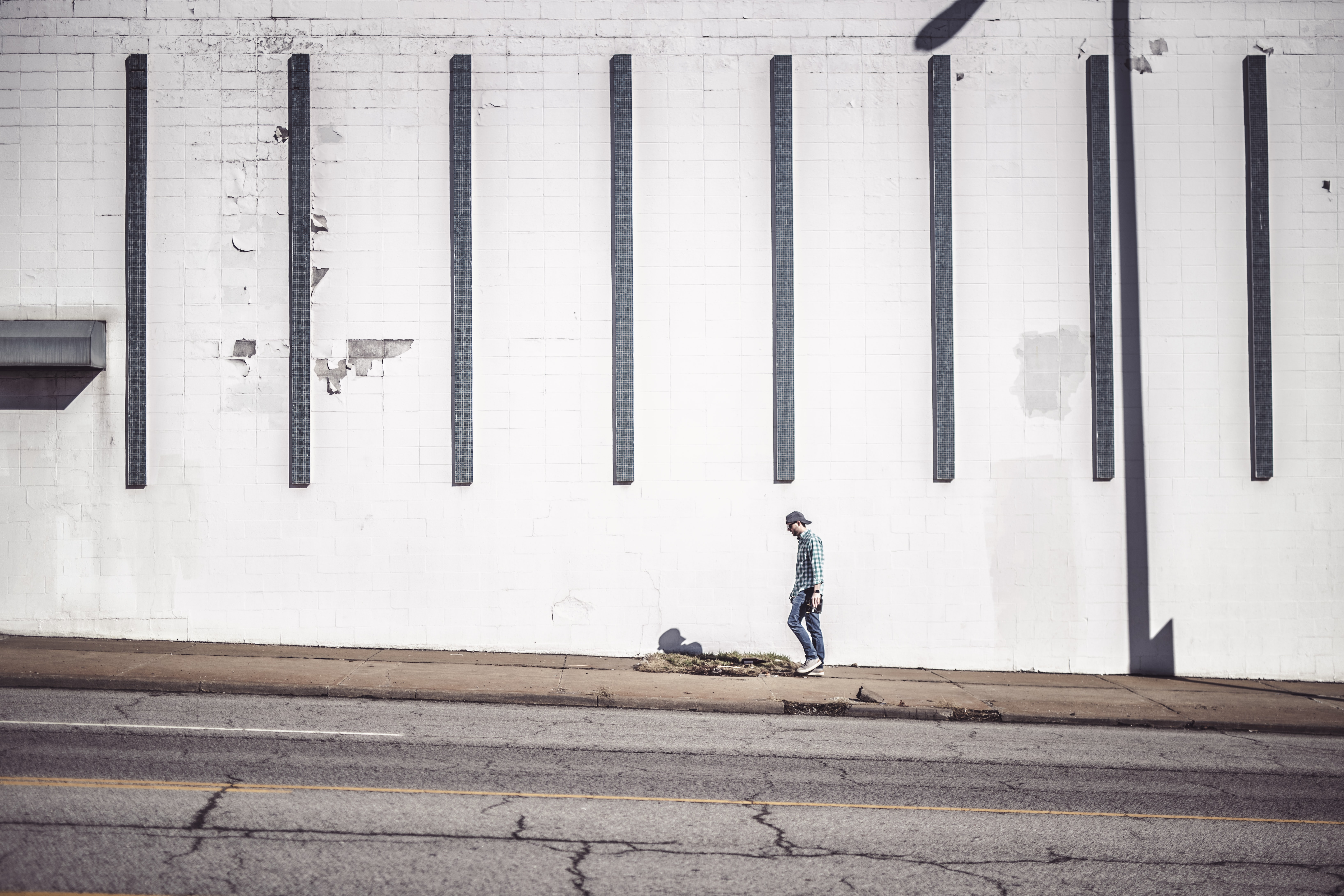 man walking at the side of the road beside wall