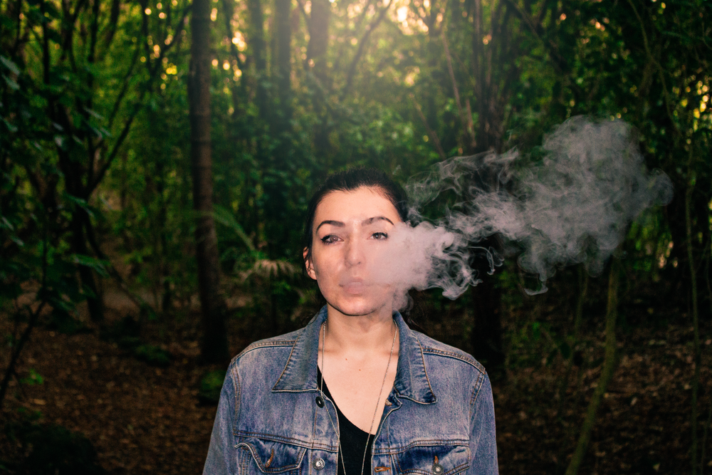 smoking woman wearing blue denim jeans standing in the middle of foreset