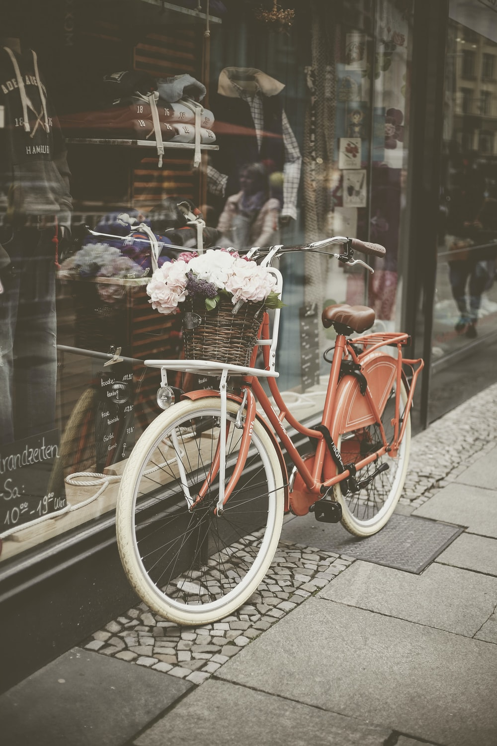 red step through bicycle parked on glass wall