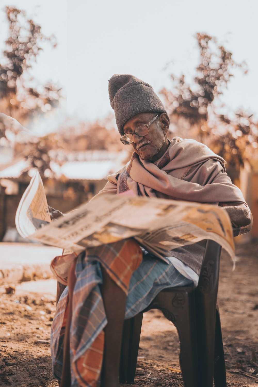 shallow focus photo of man reading newspaper