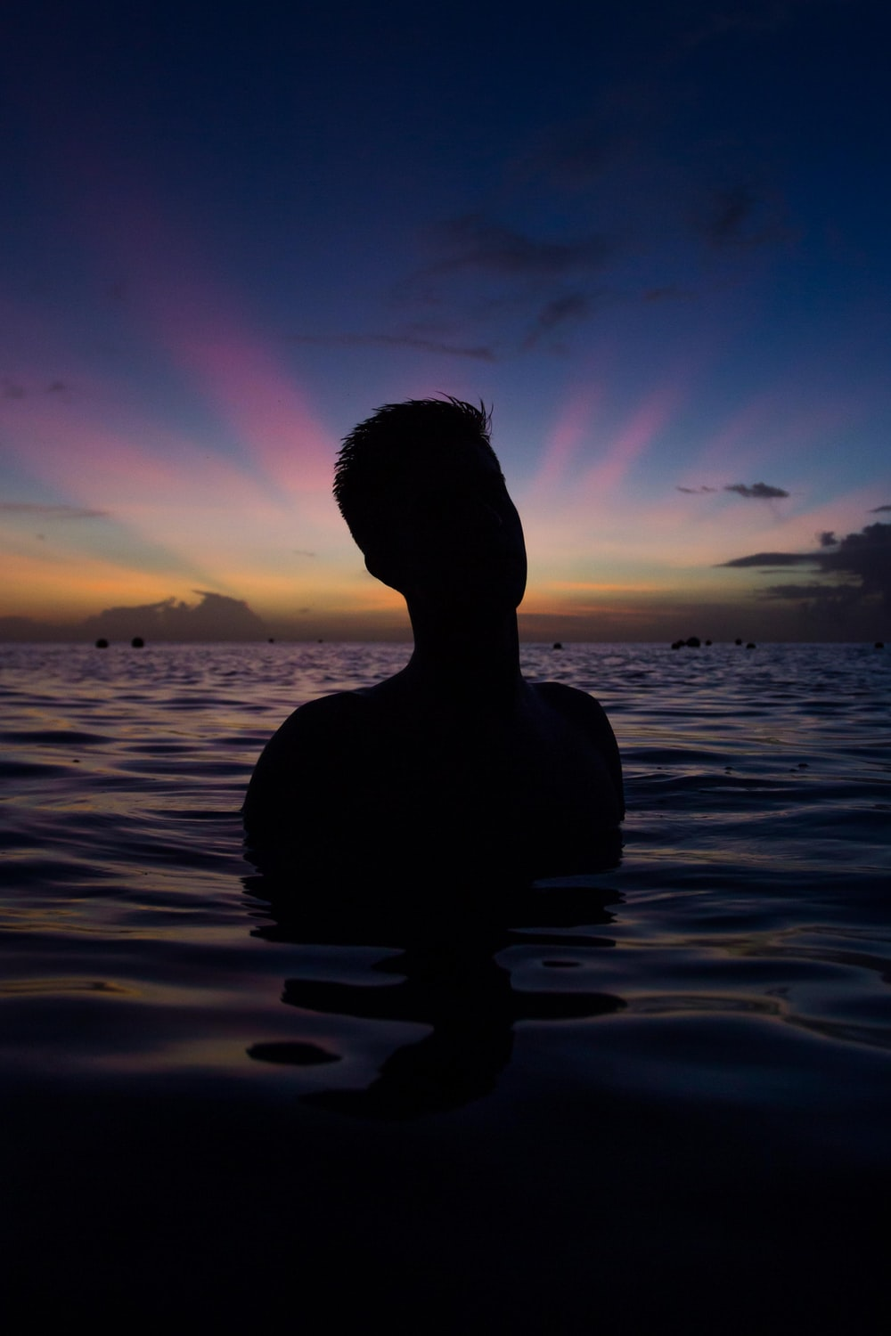 person in body of water during golden hour