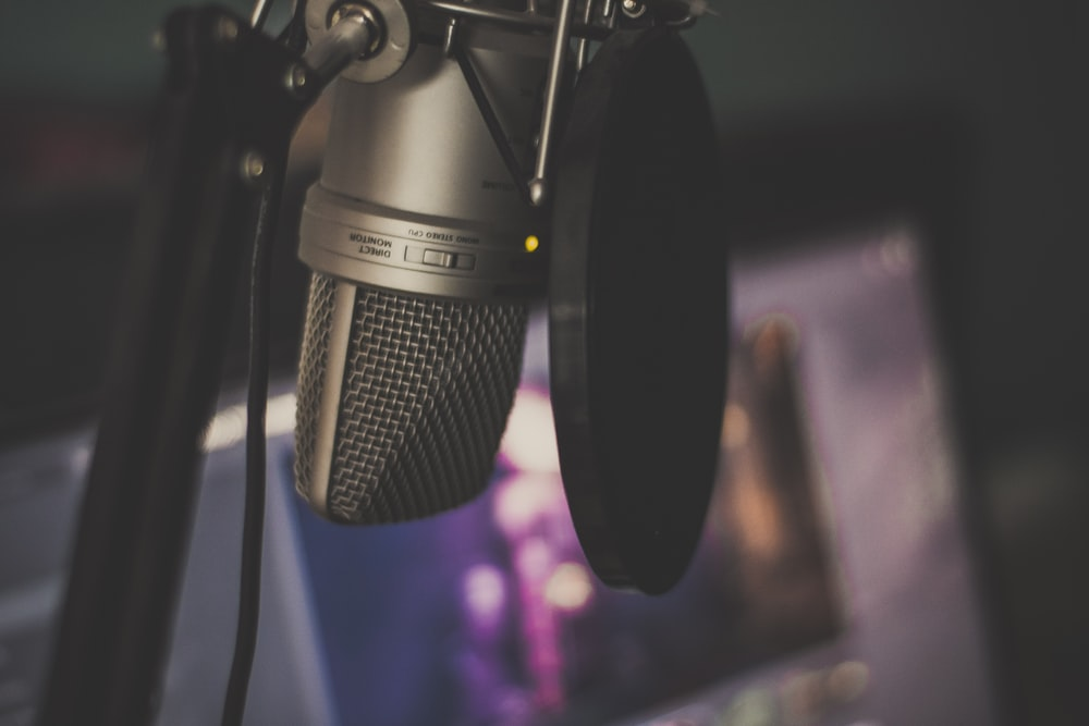 focus photography of gray condenser microphone and pop filter