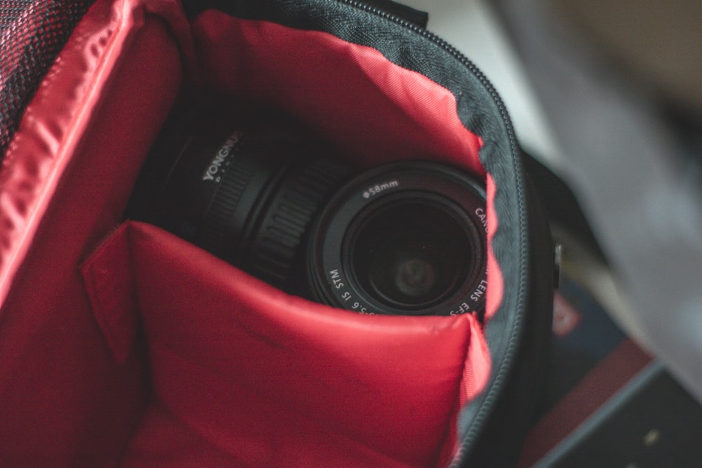 shallow focus photo of black camera lens on black and red bag