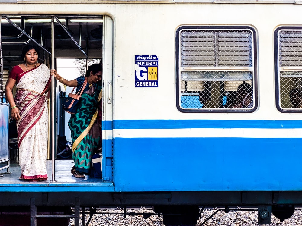 woman standing inside white and blue train