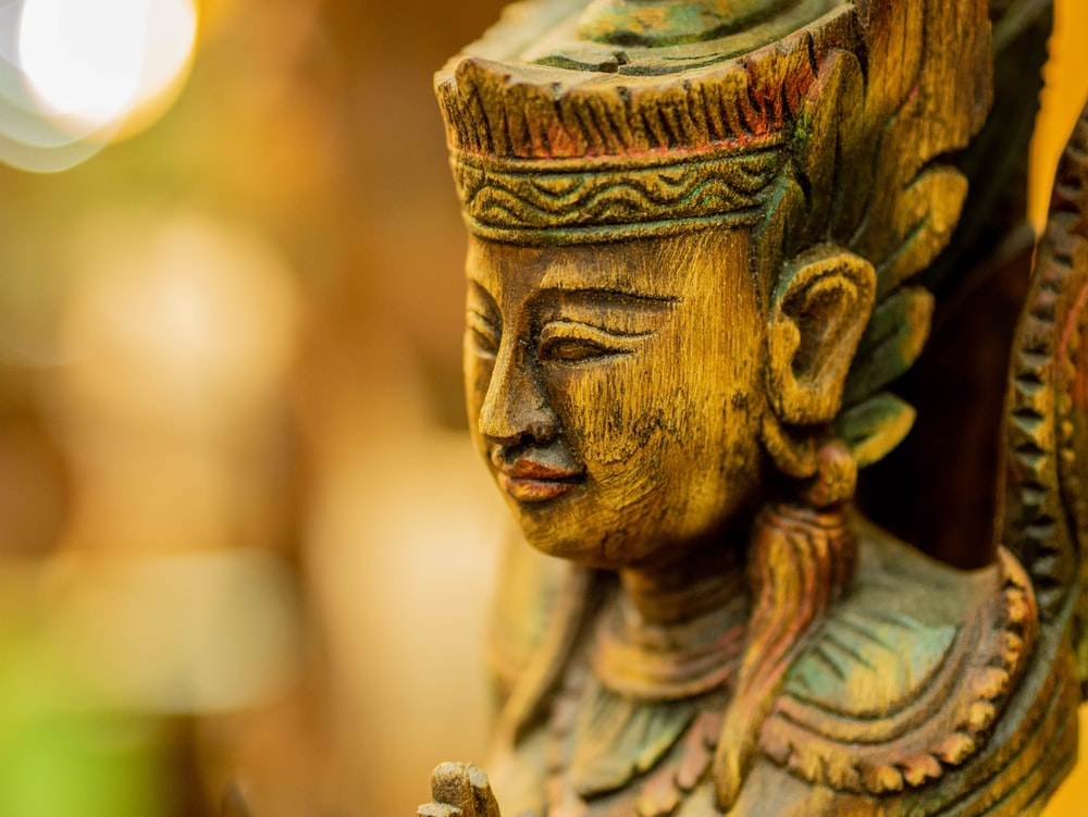 brown carved deity statue in selective focus photography