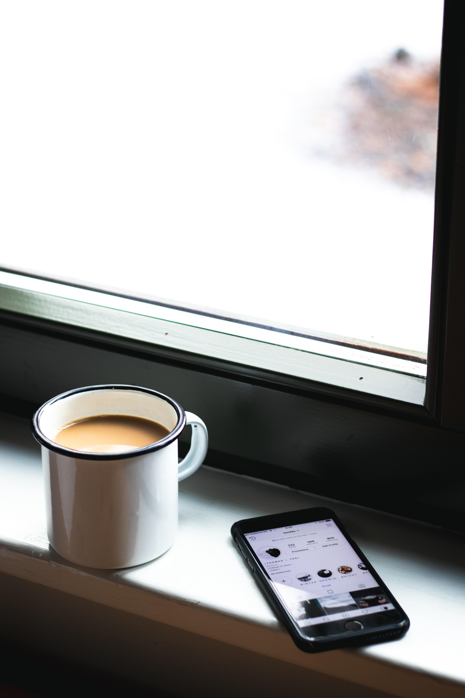 shallow focus photo of white ceramic mug beside space gray iPhone 6
