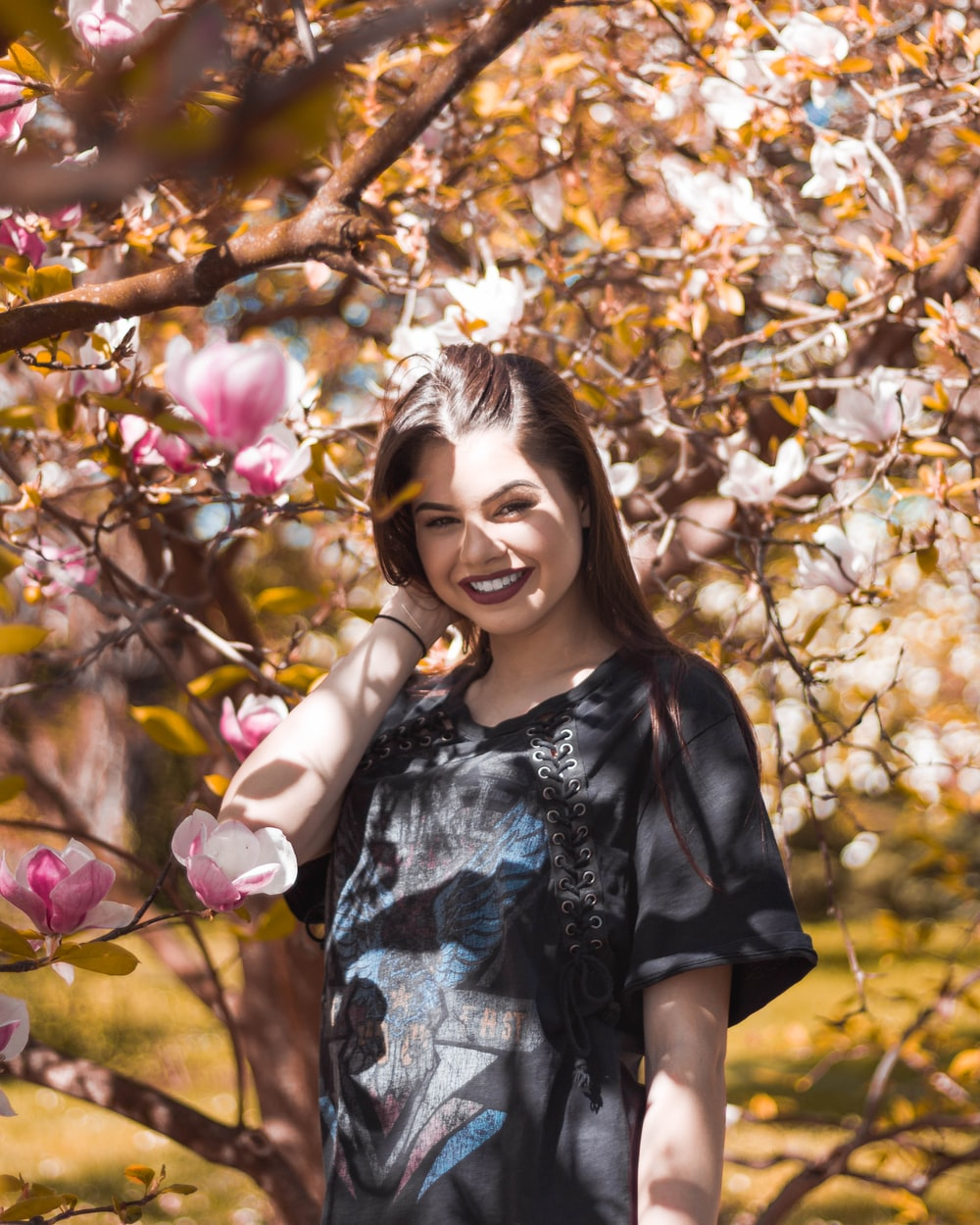 woman smiling under pink flower tree