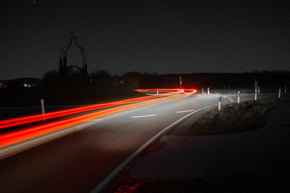time-lapse photography of passing vehicles on road