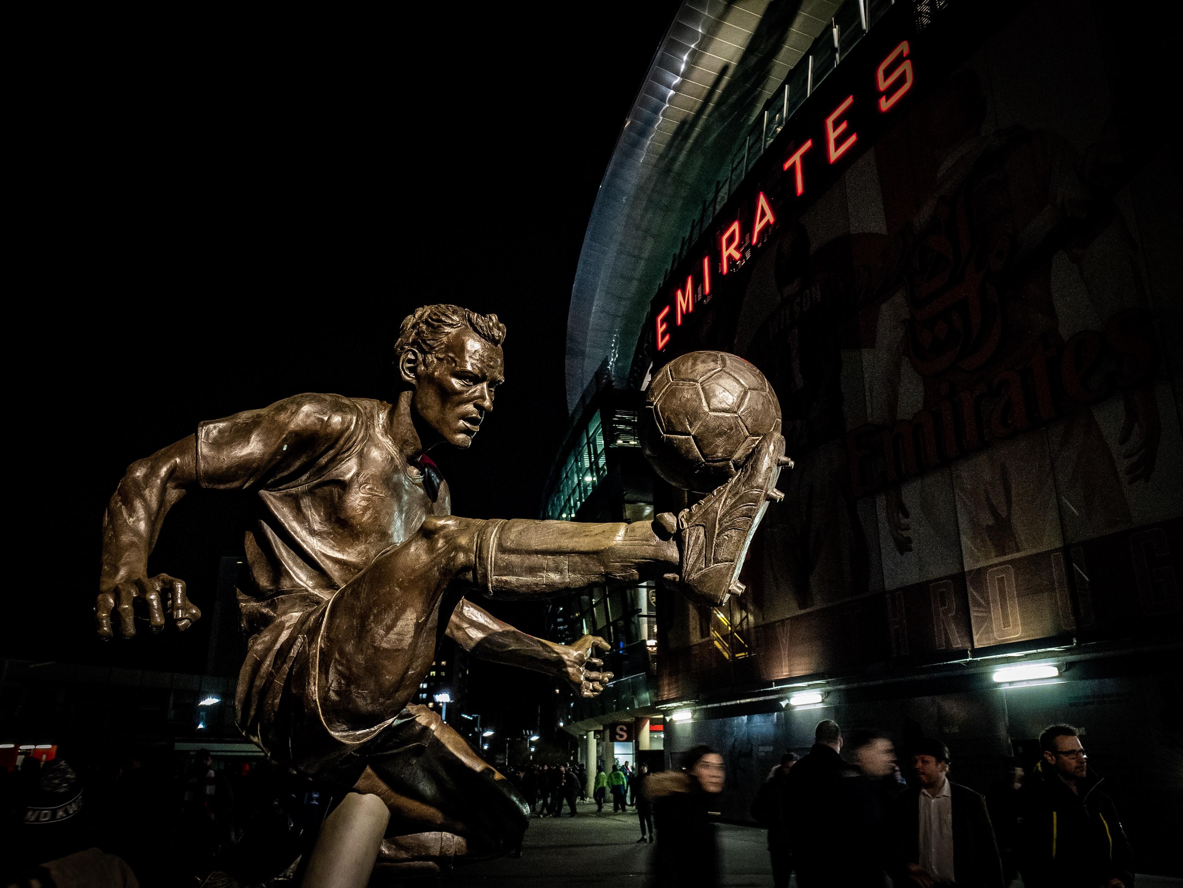 man playing soccer ball statue
