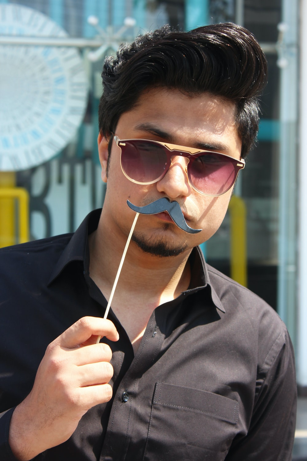 man holding black mustache party props