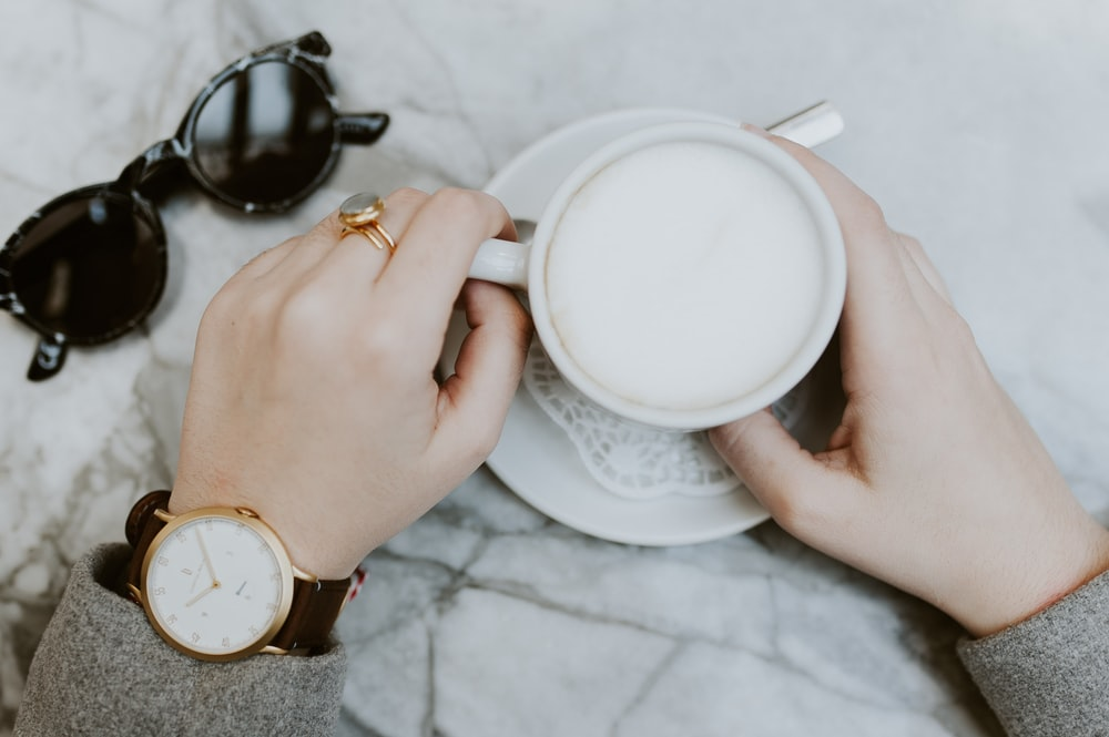 person holding filled white teacup