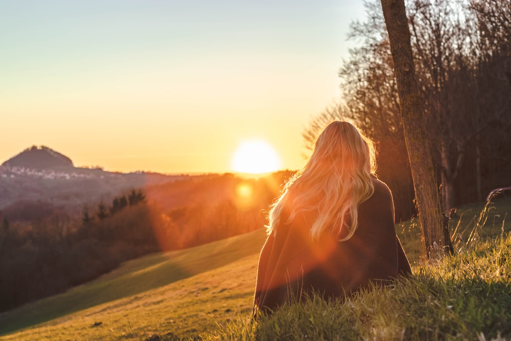 woman sitting on green grass looking at the sun