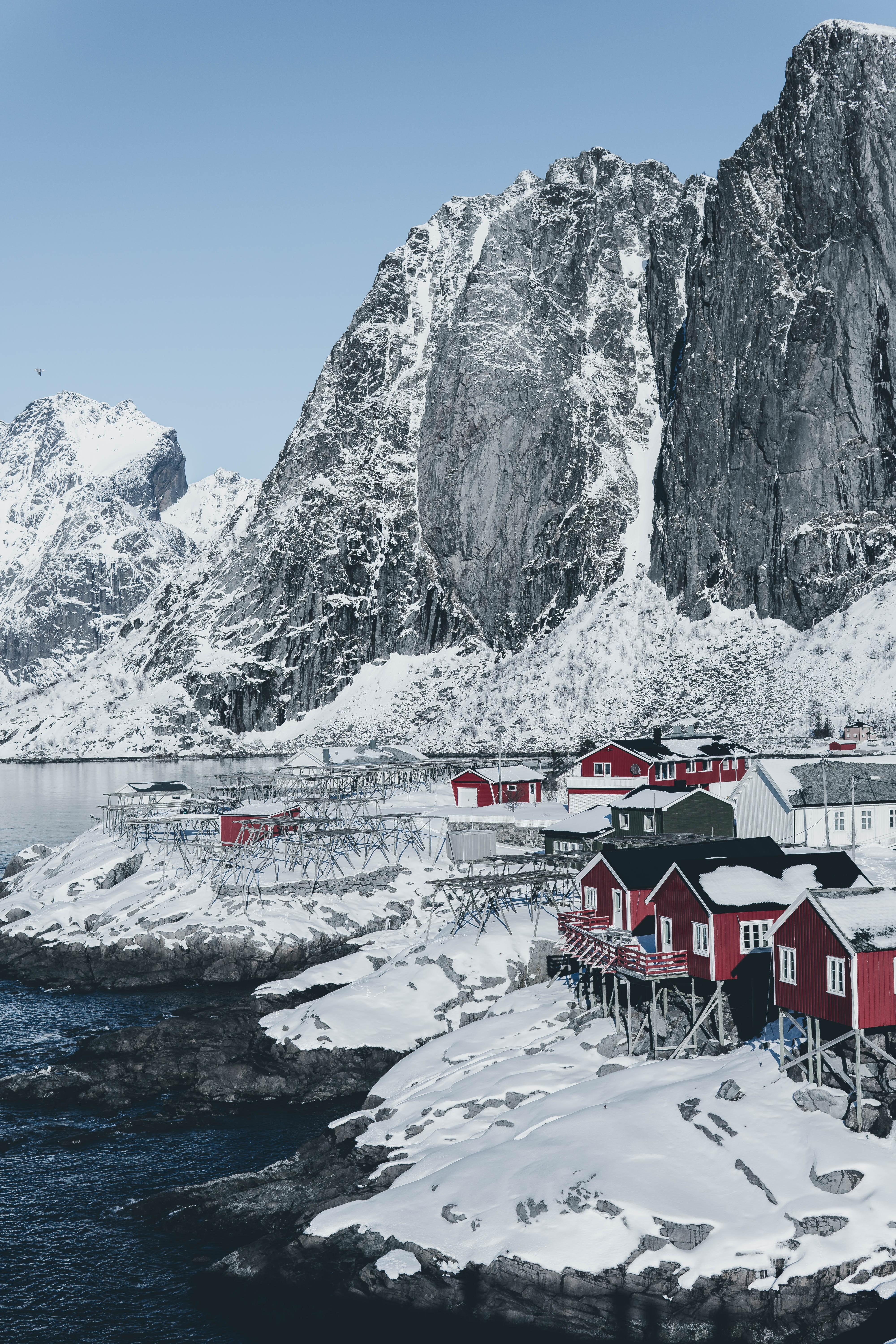 houses near body of water covered by snow