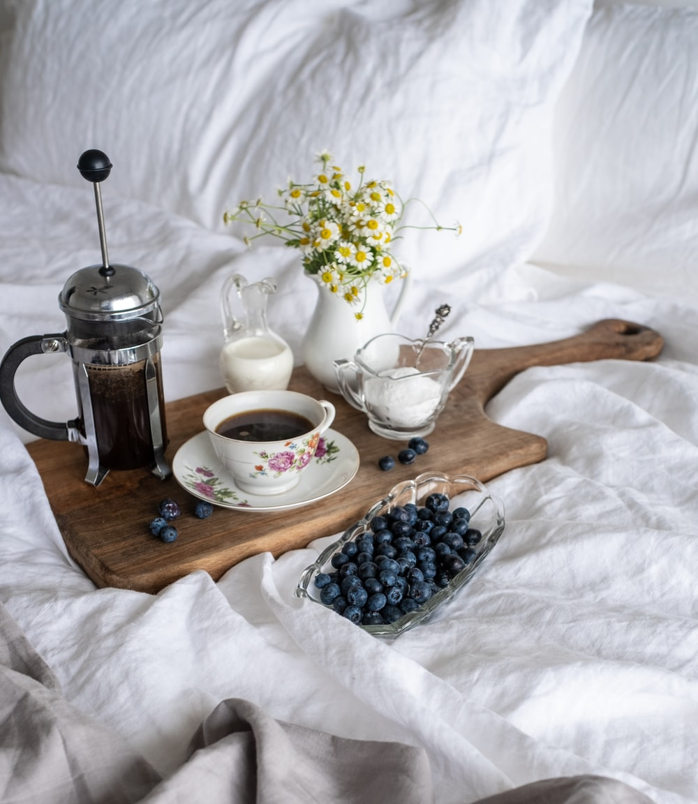 cup of coffee in between of coffee press and glass of sugar and milk on brown tray