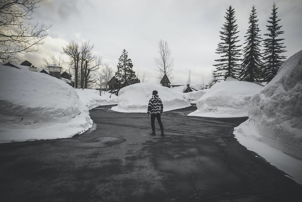 grayscale photography of man surrounded by snow