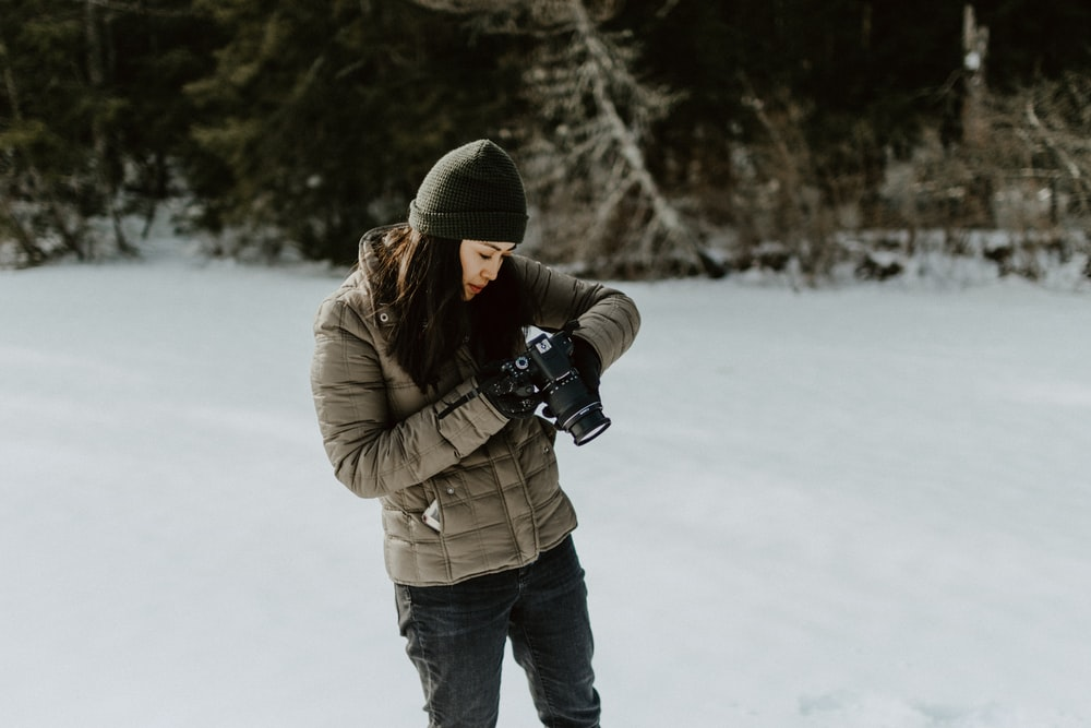 woman holding black digital camera standing on ground filled with snow