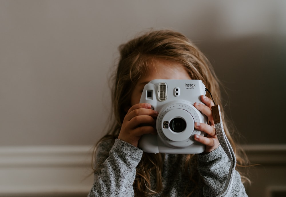girl taking a picture using instant camera