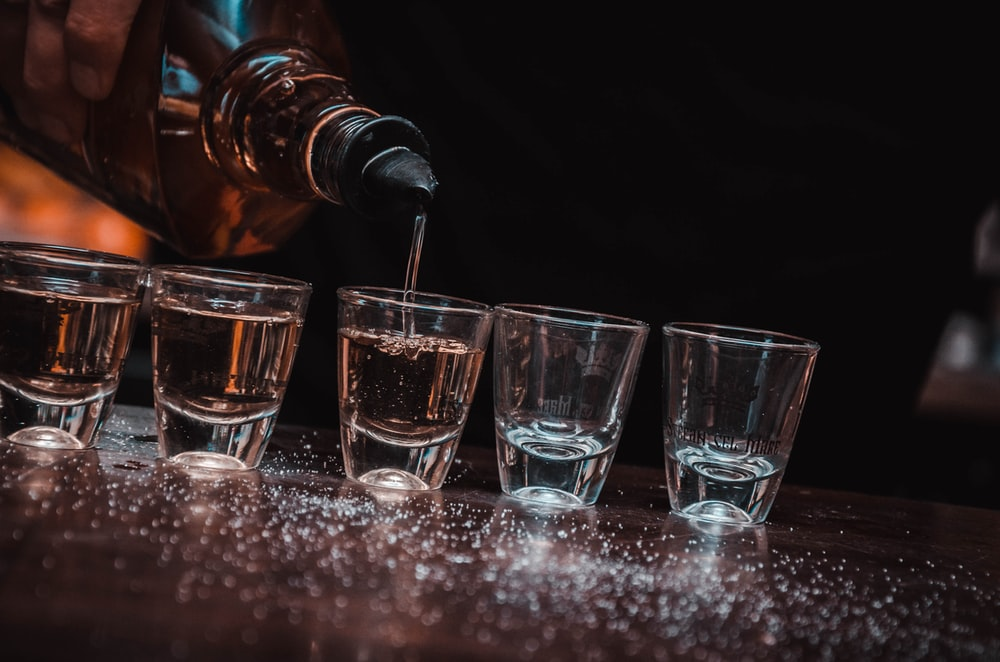 person pouring beverage on five shot glasses