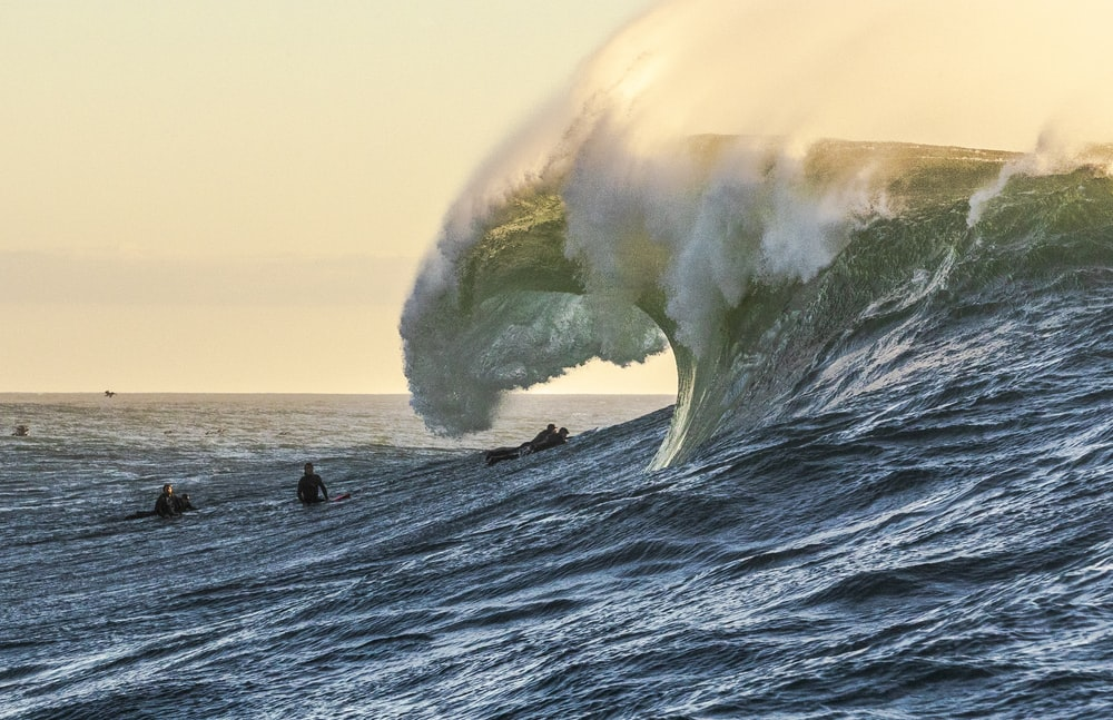surfers with approaching ocean wave during daytime