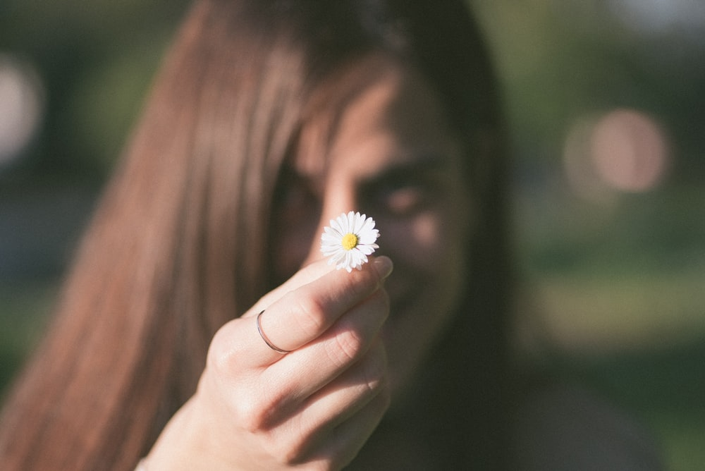selective focus photo of woman holding white aster flower