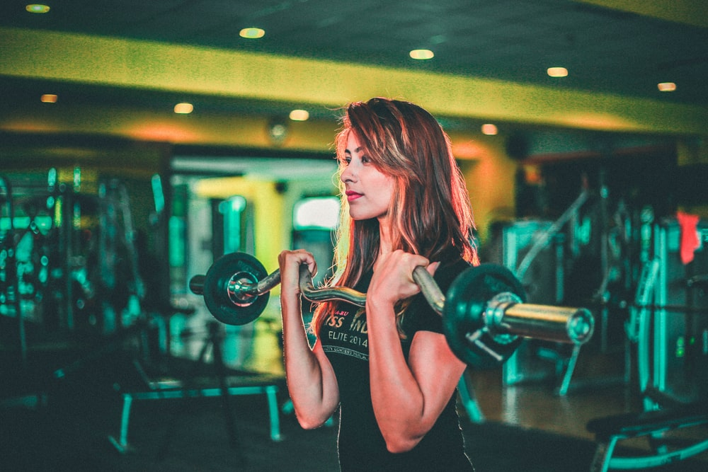woman lifting black and gray barbell,जिम का बिजनेस,Gym Business Ideas
