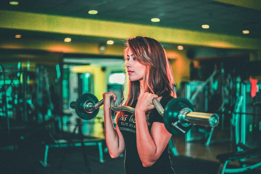 woman lifting black and gray barbell