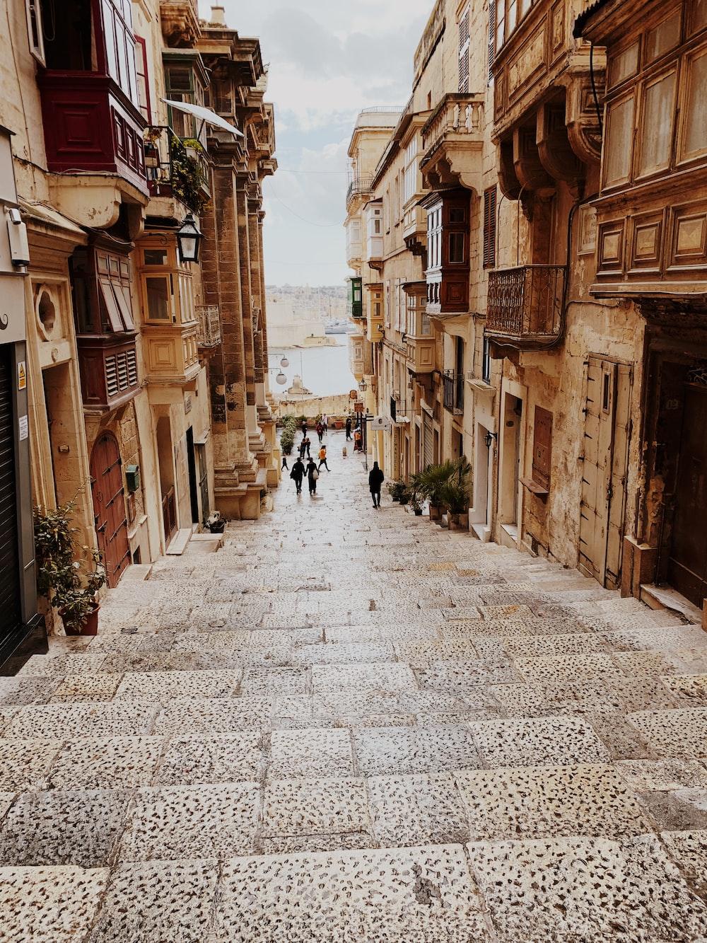 people walking on stairs between brown buildings during daytime