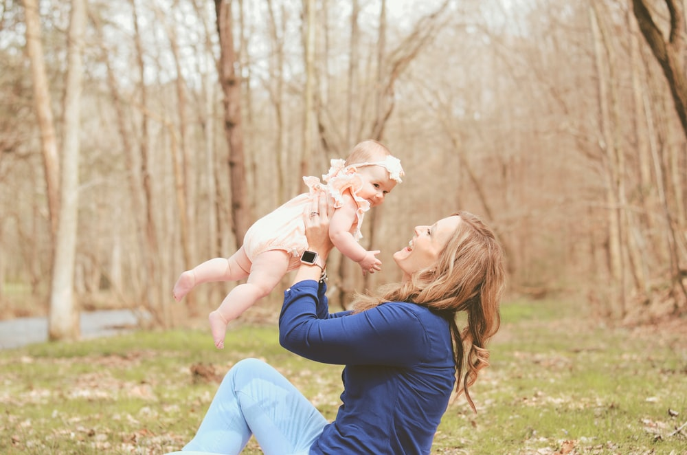 woman carrying child while sitting on ground