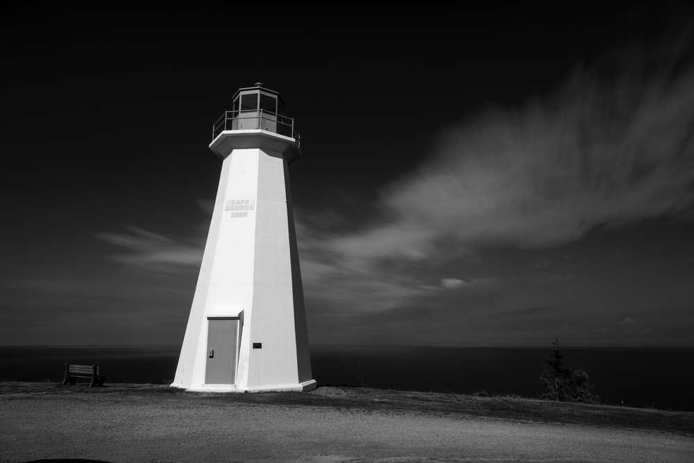 white concrete lighthouse grayscale photography