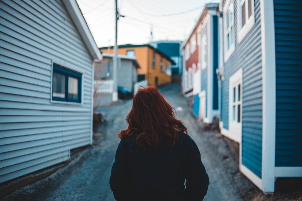 woman standing between houses