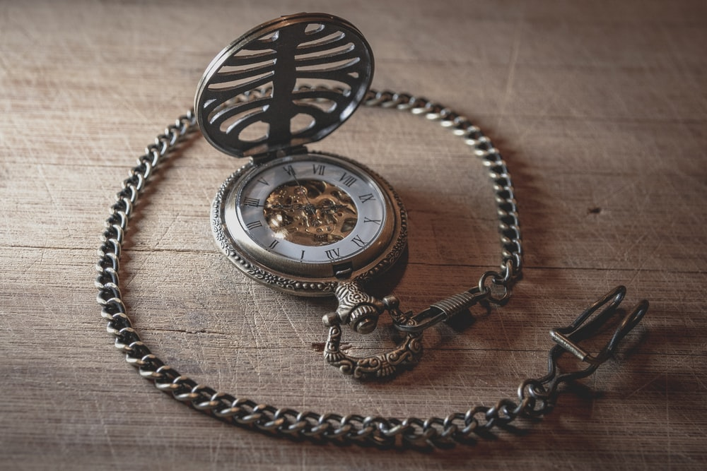 round silver-colored pocket watch on table