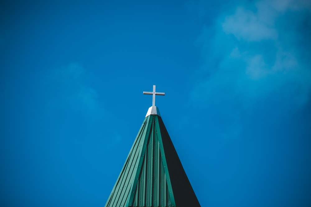 white concrete cross under clear blue sky