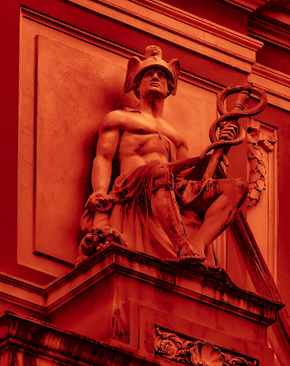 man holding rod statue