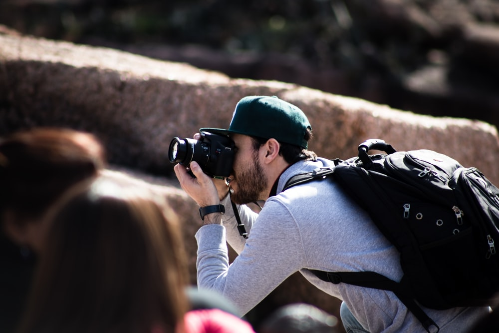 man taking photo beside rock formation