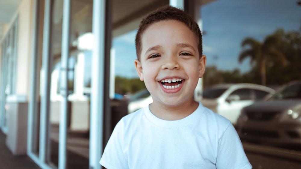 smiling boy wearing white crew-neck t-shirt during daytime